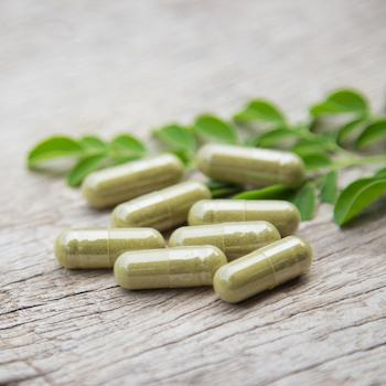 Green pills and small leaves on wooden surface