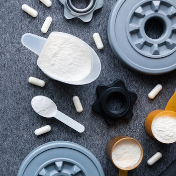 Creatine supplement powder in scoops, pills, and weight plates