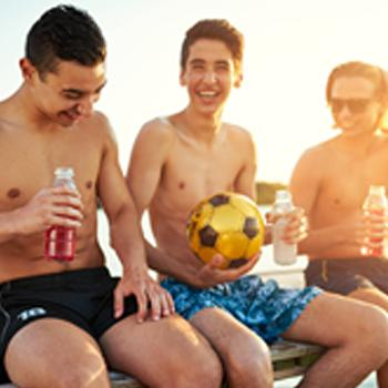 Boys in swim trunks sitting on bench with drink bottles