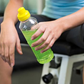 Person in workout clothes holding drink bottle with green liquid