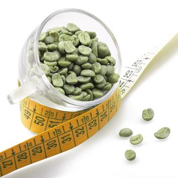 Green coffee beans in cup with measuring tape wrapped around