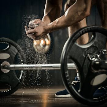 Weight lifter getting ready to lift barbell with heavy weights