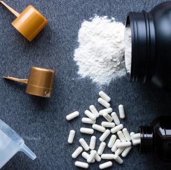Pills and powder in supplement bottles with scoops