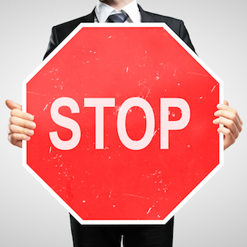 Man in suit holding stop sign