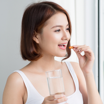 Woman taking pill holding glass of water