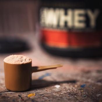 Whey protein container and scoop filled with brown powder