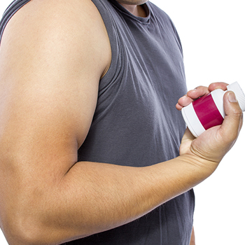 Man's hand holding supplement bottle