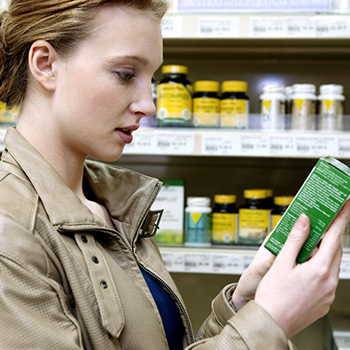 Woman looking at supplement label